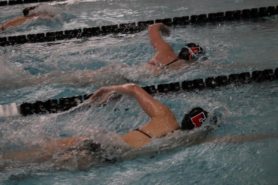 Two girls from the team swimming freestyle.