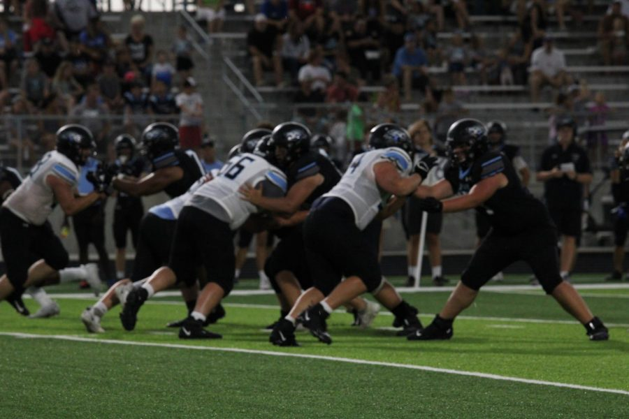 The Wolves linemen push and shove as the play begins