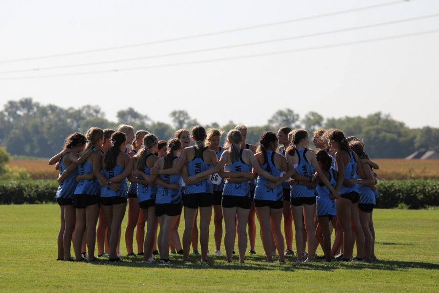 The girls cross country team huddled up right before the race.
