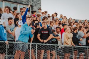 The crowd celebrates and gets excited for the upcoming football game and homecoming dance.