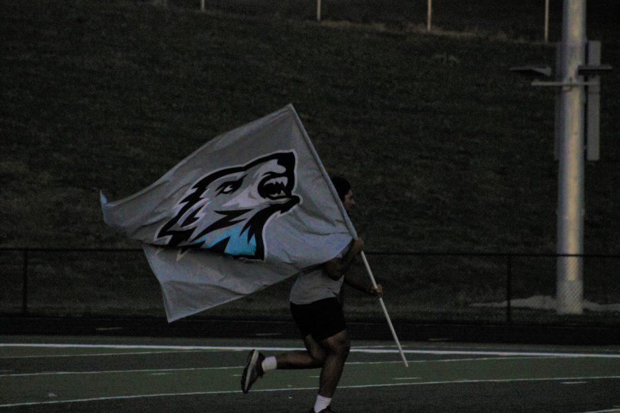 Senior Shan Acharya runs with the Elkhorn North flag.